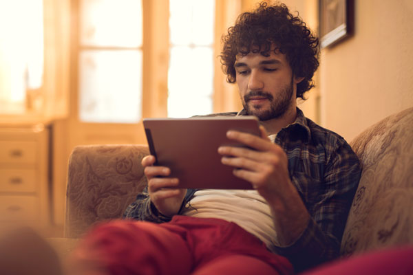 man reading an eboook on a tablet